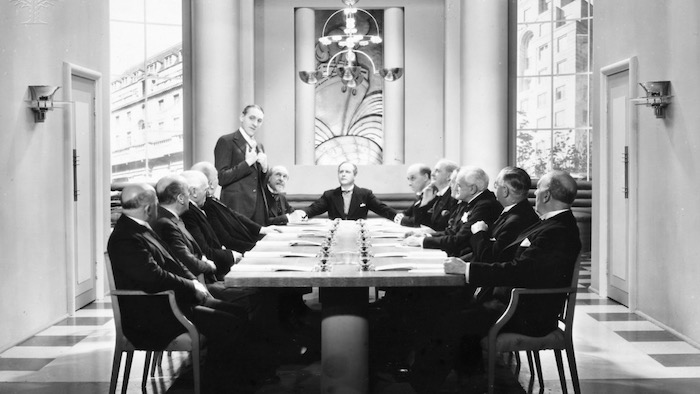 Still from a 1920 silent movie, board meeting - Britannica ImageQuest