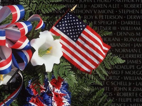 Vietnam Memorial with floral wreath and flag - Britannica ImageQuest