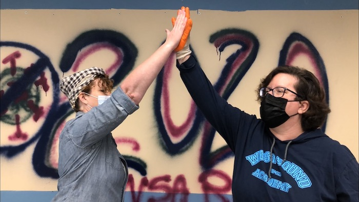 Barrie and Lisa give high fives during the tear-down project